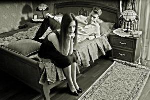 Streit in der Fernbeziehung - Pärchen diskutiert auf dem Bett